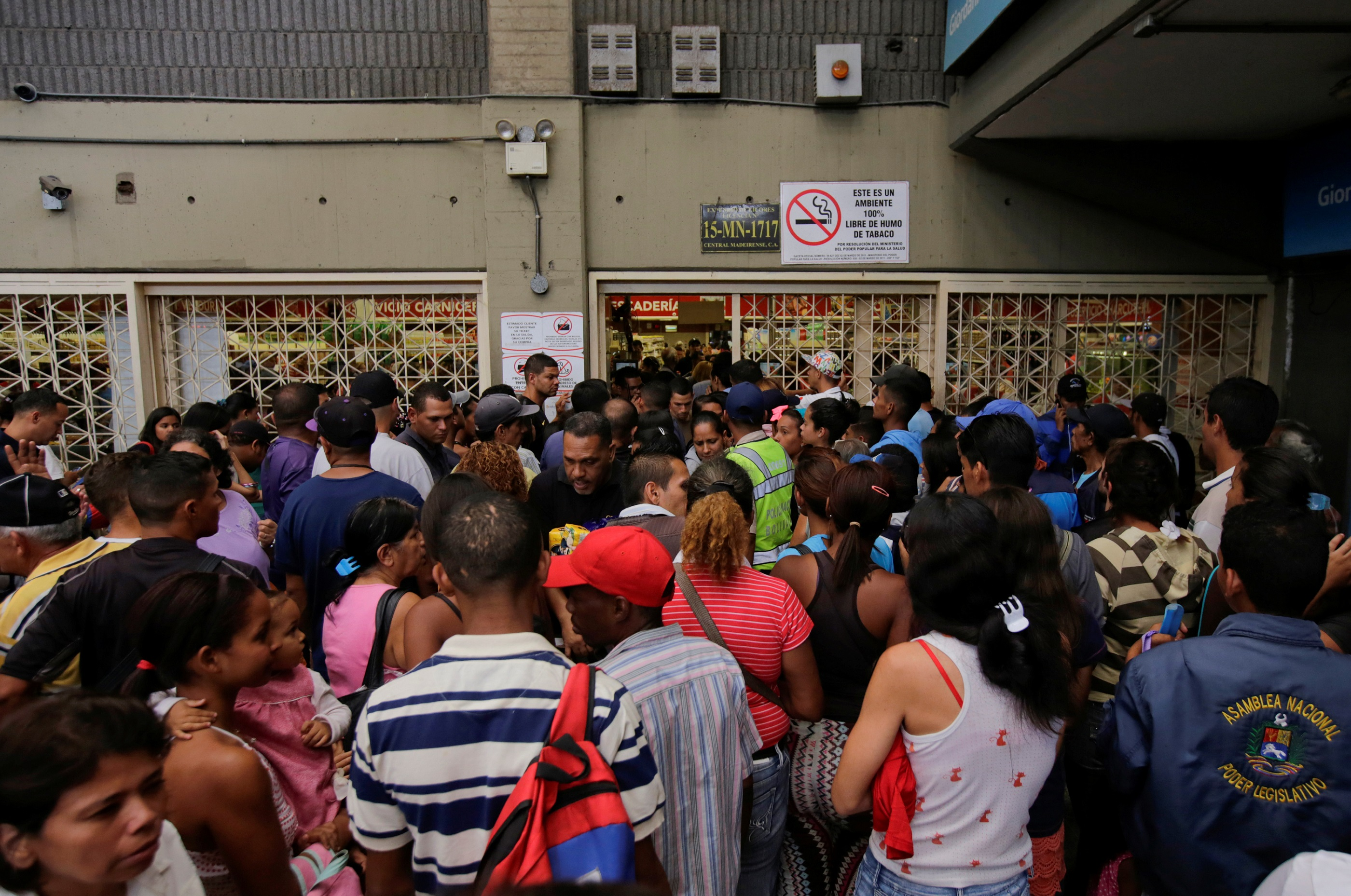 People wait to buy staple items and basic food outside a supermarket in Caracas, Venezuela. Reuters/Henry Romero