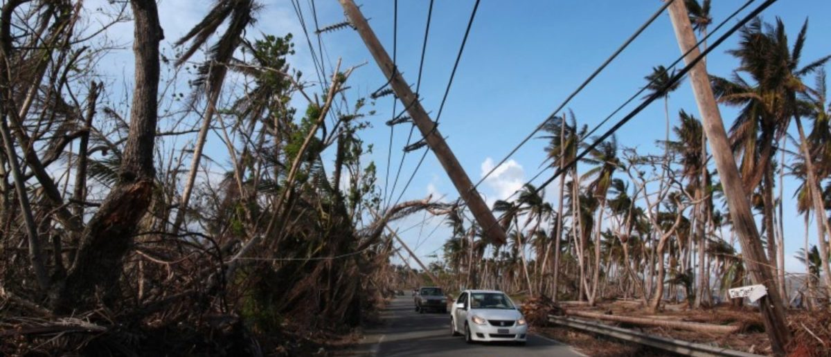 FILE PHOTO: Cars drive under a partially collapsed utility pole, after the island was hit by Hurricane Maria in September, in Naguabo, Puerto Rico. (Photo: REUTERS/Alvin Baez)