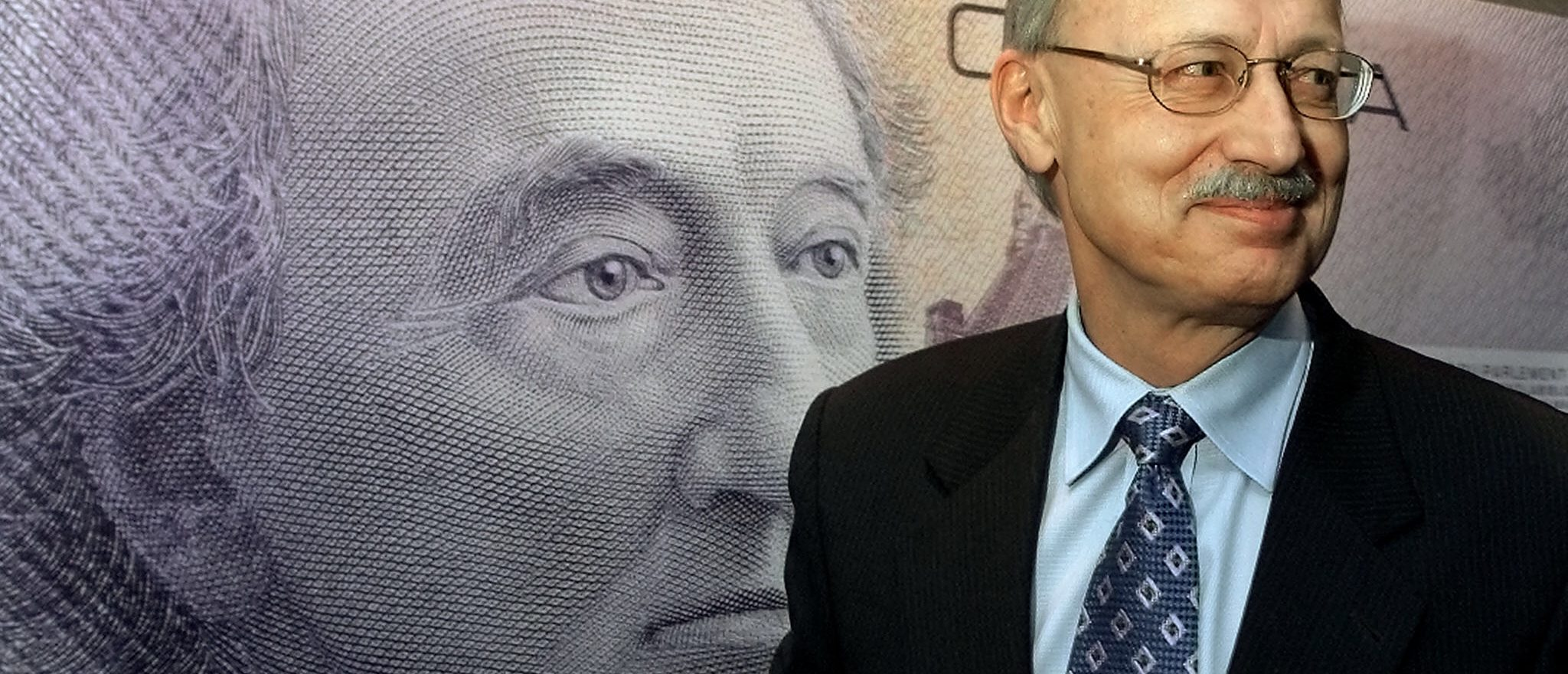 FILE -- Governor of the Bank of Canada Gordon Thiessen walks past the design of the new Canadian 10 dollar bill in Ottawa, January, 17, 2001. The bill depicts a new portrait of former Canadian Prime Minister Sir John A. MacDonald. REUTERS