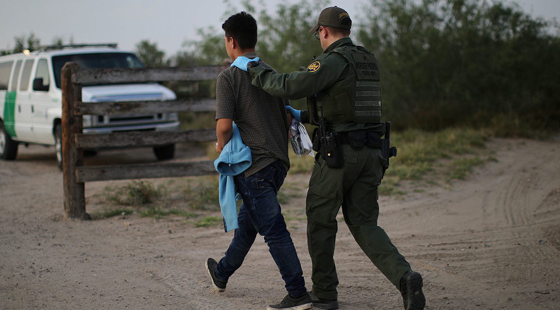 A U.S. border patrol agent detains a man after entering the United States by crossing the Rio Grande river from Mexico, in Roma, Texas, U.S., May 11, 2017. REUTERS/Carlos Barria