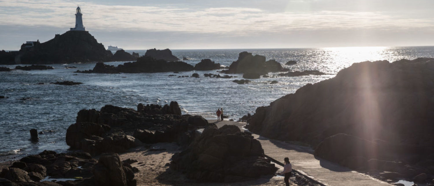 ST HELIER, JERSEY - APRIL 13: The sun begins to set over Corbiere Lighthouse on April 13, 2017 near St Helier, Jersey. Jersey, which is not a member of the European Union, is one of the top worldwide offshore financial centres, described by some as a tax haven, as it attracts deposits from customers outside of the island who seek the advantages of reduced tax burdens. In 2008 Jersey's gross national income per capita was among the highest in the world. However, its taxation laws have been widely criticised by various people and groups including the EU. (Photo by Matt Cardy/Getty Images)