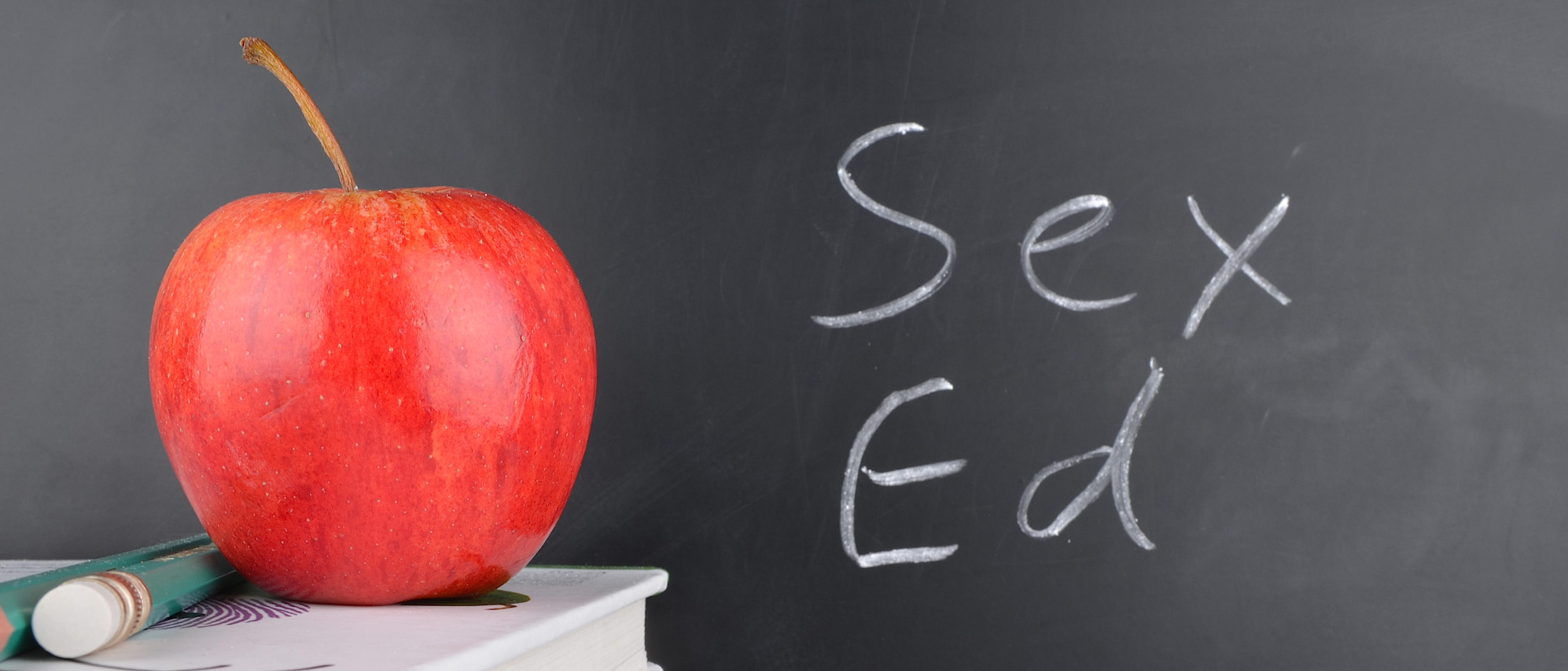 Classroom with red apple,books and handwriting. (Shutterstock/simez78)