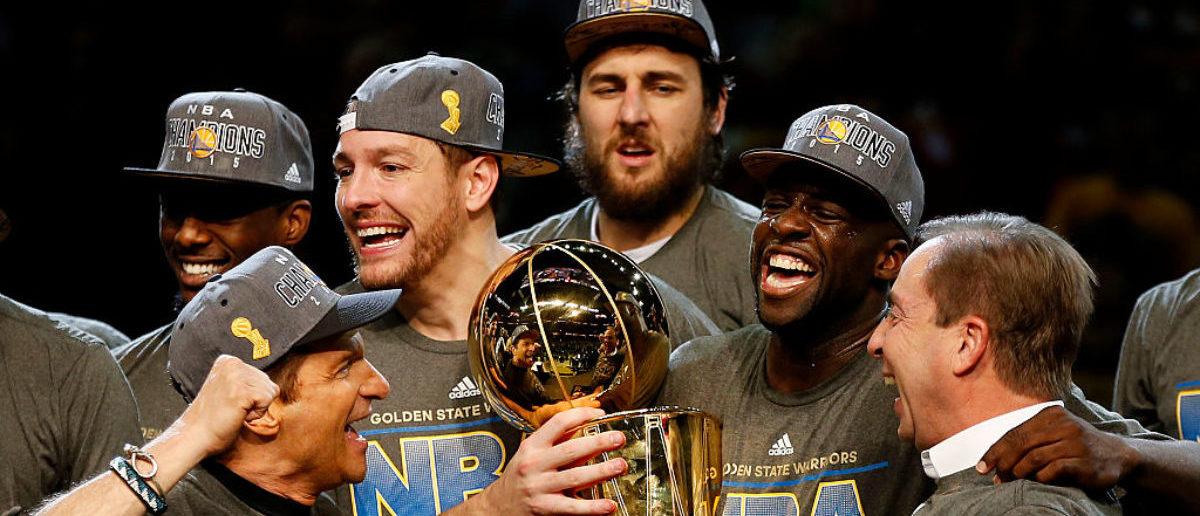 CLEVELAND, OH - JUNE 16: Draymond Green #23 David Lee #10 and Andrew Bogut #12 of the Golden State Warriors celebrates with team owners Peter Guber and Joe Lacob and the Larry O'Brien NBA Championship Trophy after defeating the Cleveland Cavaliers 105 to 97 to win Game Six of the 2015 NBA Finals at Quicken Loans Arena on June 16, 2015 in Cleveland, Ohio. (Photo by Ezra Shaw/Getty Images)