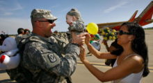 1st Lt. Keith Wolowodiuk hugs his five-month-old baby girl Kaitlyn, whom he was met once while on leave, and his wife Adrienne Wolowodiuk. (Photo by David McNew/Getty Images)