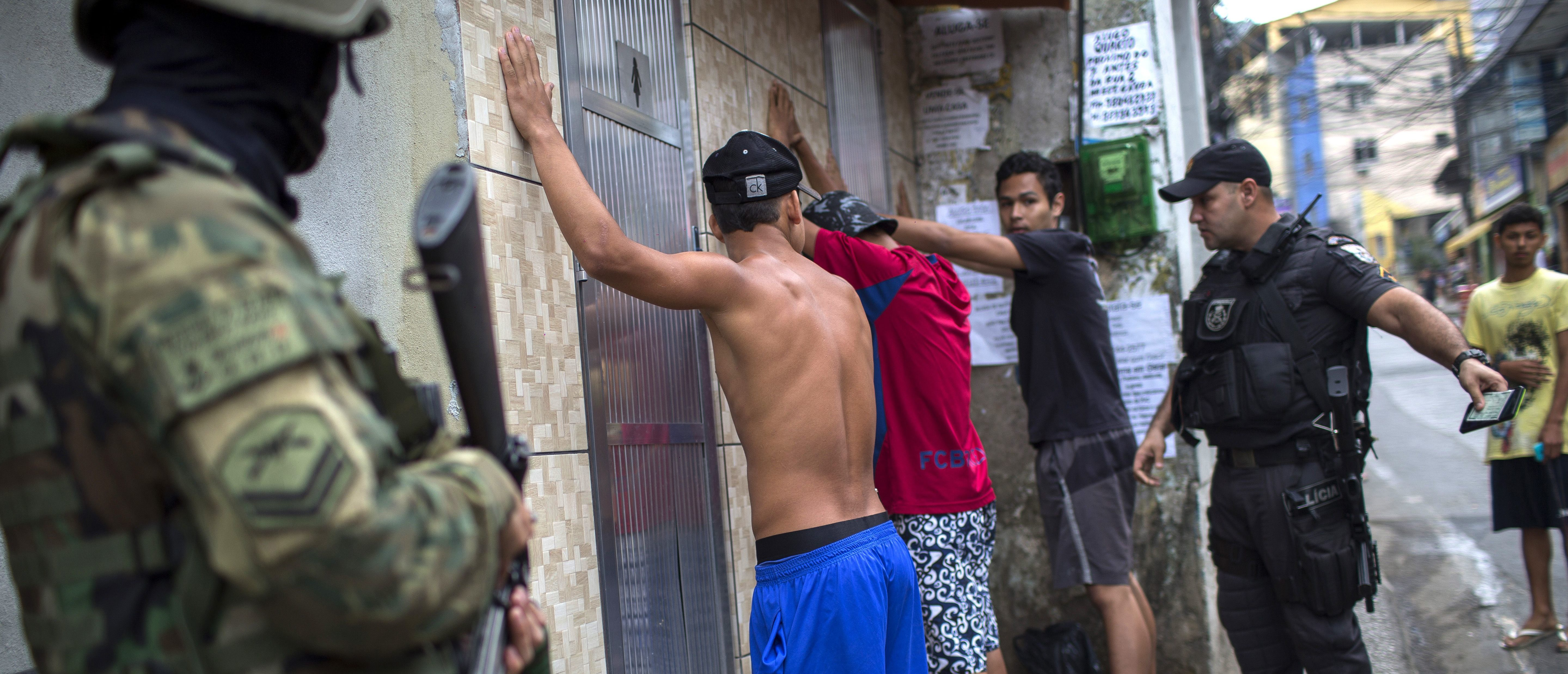Brazilian marines and police special forces personnel check the IDs of three youngster during a patrol along a street of the Rocinha favela in Rio de Janeiro, Brazil on September 24, 2017.