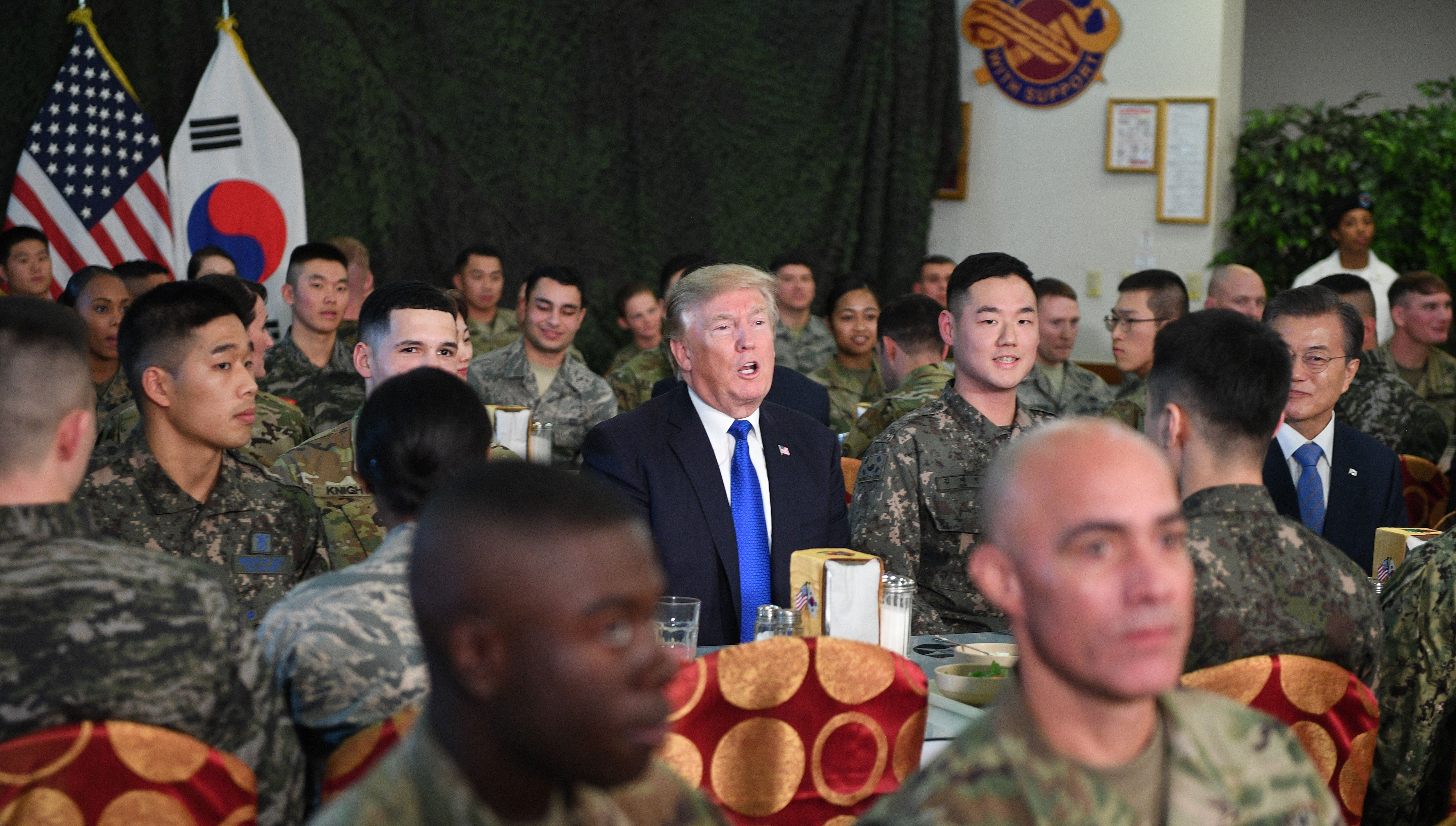 US President Donald Trump (C) talks to military personnel while South Korean President Moon Jae-In (R) looks on at Camp Humphreys in Pyeongtaek, south of Seoul on November 7, 2017. Trump's marathon Asia tour moves to South Korea, another key ally in the struggle with nuclear-armed North Korea, but one with deep reservations about the US president's strategy for dealing with the crisis. JIM WATSON/AFP/Getty Images