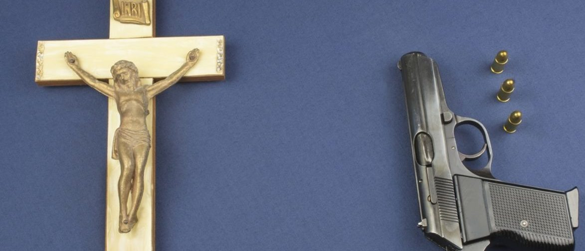 Gun And Crucifix (shutterstock/Marsan)