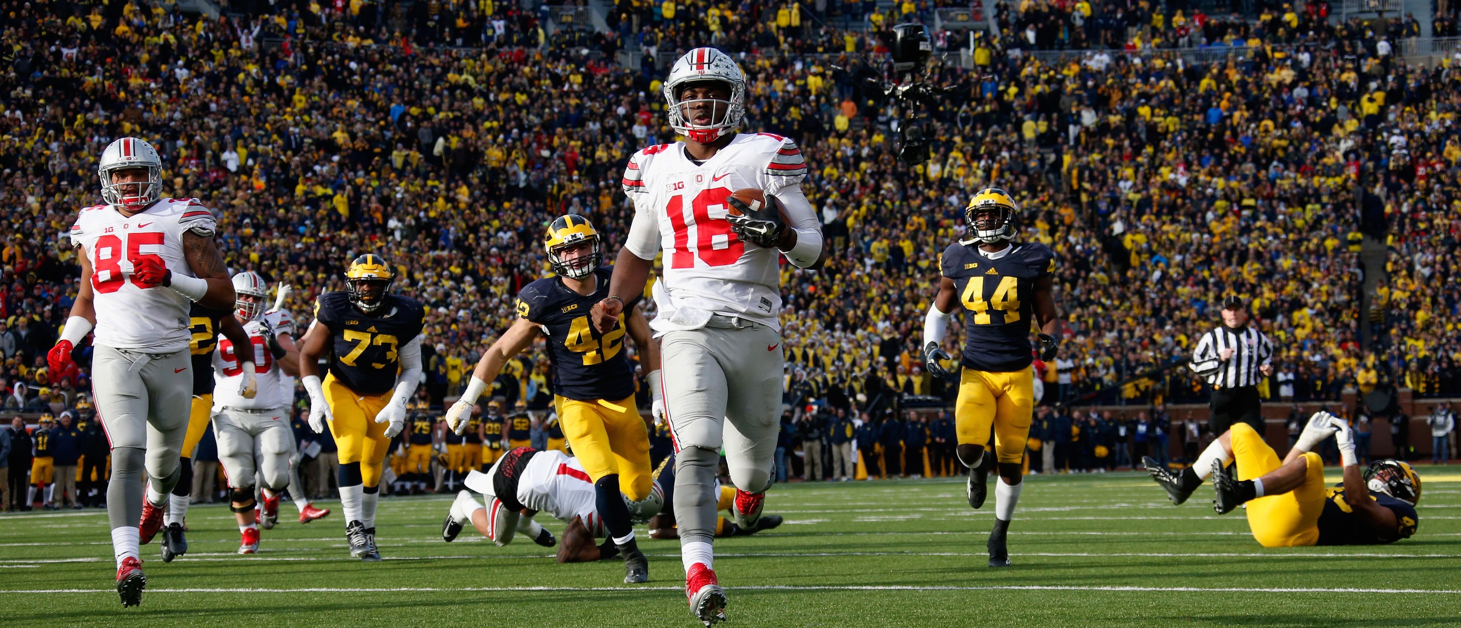 Quarterback J.T. Barrett #16 of the Ohio State Buckeyes rushes for a fourth quarter touchdown against the Michigan Wolverines at Michigan Stadium on November 28, 2015 in Ann Arbor, Michigan. (Photo by Gregory Shamus/Getty Images)