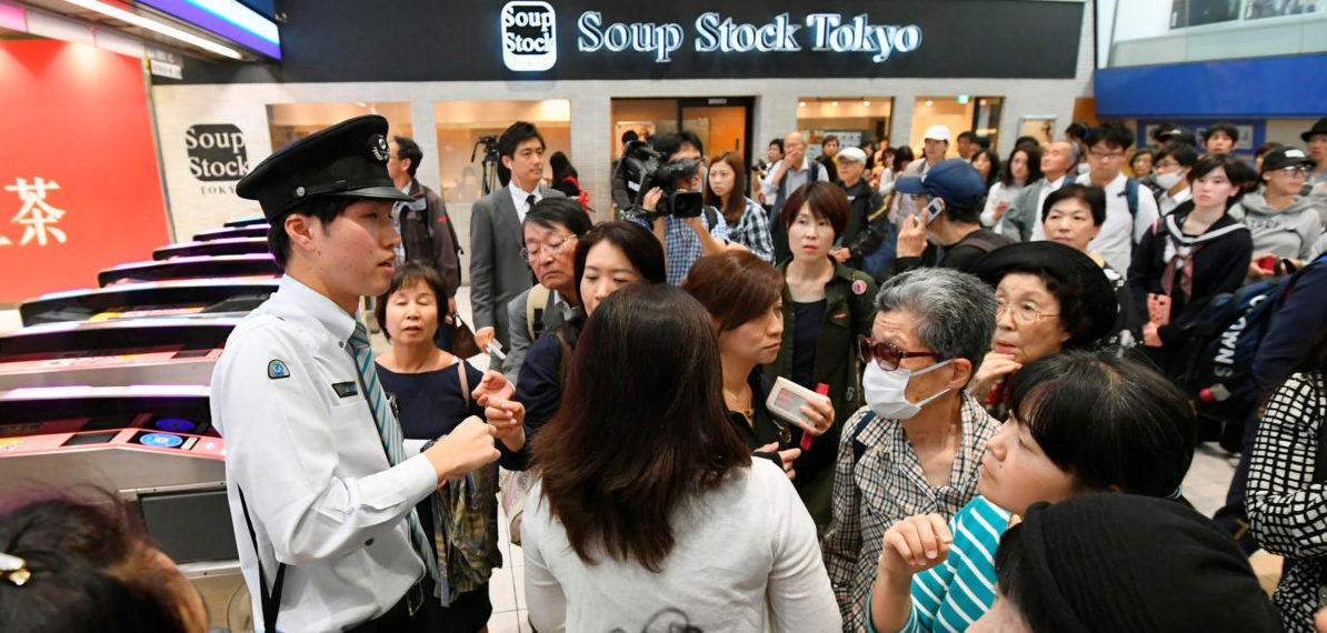 Passengers gather around a railway company staff as they try to gather information after train services were suspended because of a power outage, caused by a fire at an underground cable facility, at a station in Tokyo, Japan October 12, 2016. Kyodo/via REUTERS