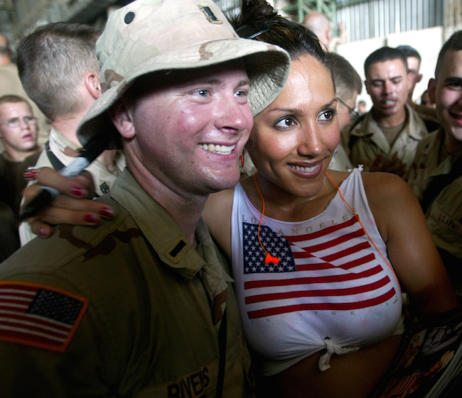 Leeann Tweeden poses with a soldier while visiting U.S. troops gathered in a helicopter hangar of Baghdad's international airport June 19, 2003. Thousands of U.S. airmen, marines, sailors and soldiers serving in Iraq were entertained by Kid Rock's band, country singer Chelly Wright, Tweeden and hip hop group Nappy Roots in a show run by the USO (United Services Overseas). REUTERS/Chris Helgren