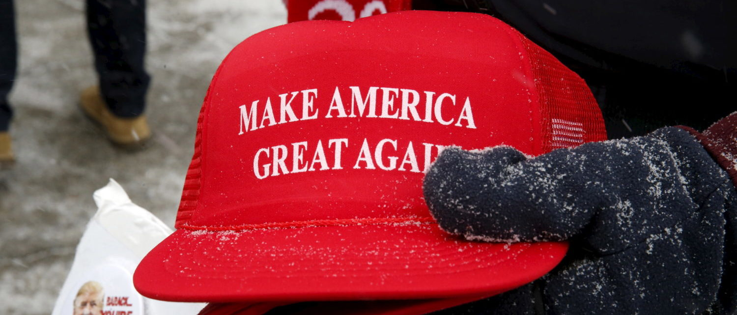 "Trump campaign merchandise vendor David Dickson from Florida holds Trump campaign ""Make America Great Again"" hats dusted with falling snow outside a Trump campaign town hall event in Londonderry, New Hampshire February 8, 2016. REUTERS/Jim Bourg - GF10000301111"