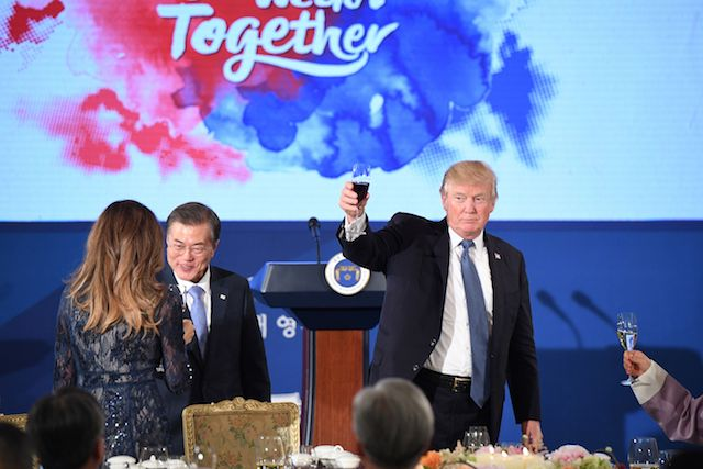 """US President Donald Trump (R) holds a glass as South Korea's President Moon Jae-In (C) talks to First Lady Melania Trump during a state dinner at the presidential Blue House in Seoul on November 7, 2017. North Korea poses a worldwide threat that requires worldwide action, President Donald Trump said in Seoul on November 7, but insisted """"we are making a lot of progress"""" in reining in the rogue state. / AFP PHOTO / Jim WATSON (Photo credit should read JIM WATSON/AFP/Getty Images)"""