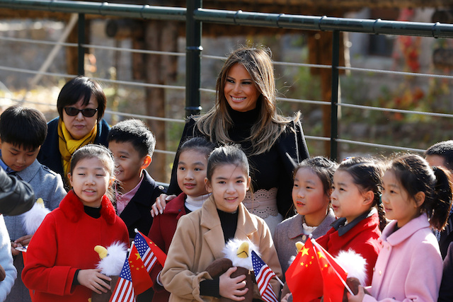 U.S. first lady Melania Trump smiles with children holding U.S. and China flags as she visits Beijing Zoo in Beijing, China, November 10, 2017. REUTERS/Thomas Peter - RC1ABEA26DB0