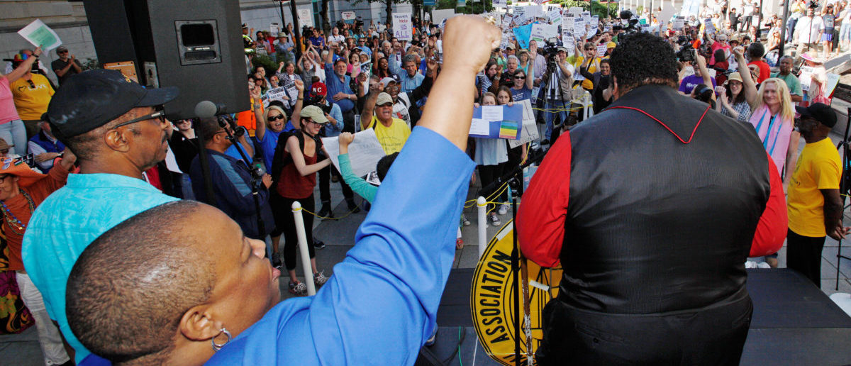 "Bishop Tonyia Rawls, the openly gay pastor of Charlotte's Sacred Souls Community Church and founder of The Freedom Center for Social Justice, raises her fist as the Reverend Doctor William Barber II (R), president of the NAACP's North Carolina chapter and leader of the ""Moral Monday"" civil rights protests, speaks against the state's HB2 ""bathroom law"" that restricts members of the LGBT community from using the bathroom of their choice, during a demonstration outside the state legislature in Raleigh, North Carolina on May 16, 2016. To match Feature USA-LGBT/BLACKS REUTERS/Jonathan Drake"