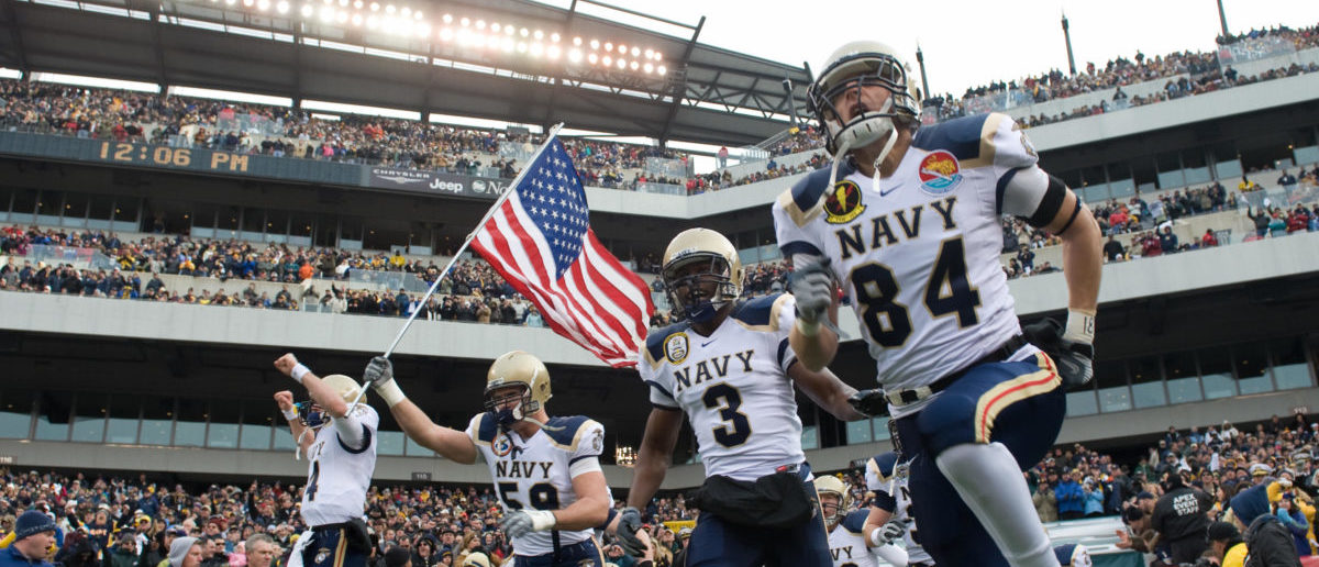 Members of the Navy football team run out onto the field prior to the Army vs. Navy football game attended by US President George W. Bush at Lincoln Financial Field in Philadelphia, Pennsylvania, on December 6, 2008. (Photo credit should read SAUL LOEB/AFP/Getty Images)