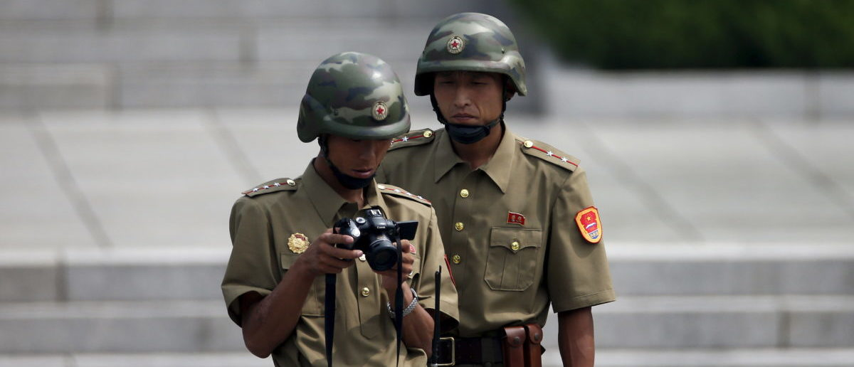 North Korean soldiers check their camera at the truce village of Panmunjom in the demilitarised zone (DMZ) separating the two Koreas, South Korea, August 11, 2015. South Korea's military on Monday threatened retaliation against North Korea after accusing the North of planting land mines inside the Demilitarised Zone border that wounded two soldiers last week, in what it called a cowardly act of provocation.  REUTERS/Kim Hong-Ji