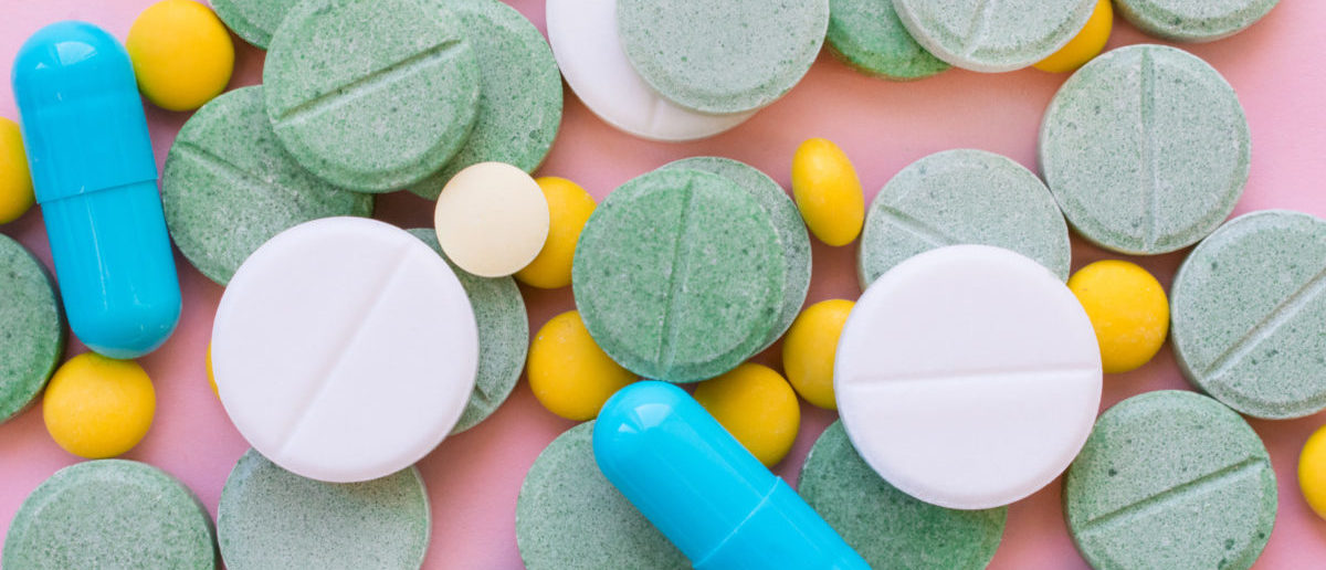 Opioid Pills. Opioid epidemic and drug abuse concept. Different tablets, pills, capsule on a pink background. Heap mix therapy drugs. (ShutterStock/Iryna Imago)