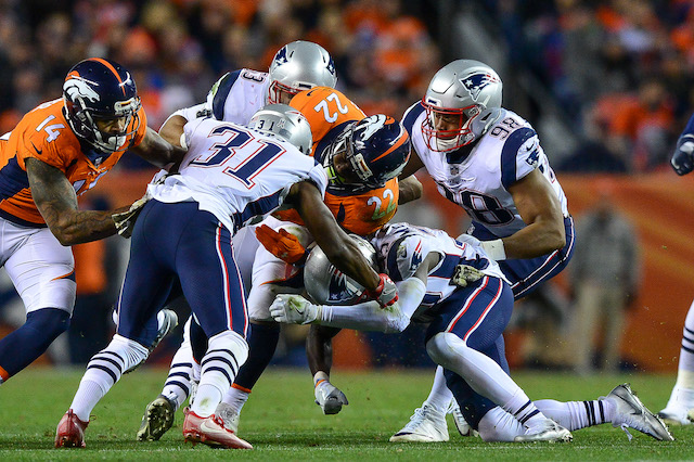 DENVER, CO - NOVEMBER 12: Running back C.J. Anderson #22 of the Denver Broncos is stopped by a group of New England Patriots players in the first half of a game at Sports Authority Field at Mile High on November 12, 2017 in Denver, Colorado. (Photo by Dustin Bradford/Getty Images)