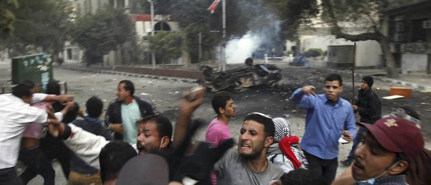 Protesters hit riot policemen (front, 2nd L and back, 3rd L) after they caught hold of them during clashes in front of the U.S. embassy, near Tahrir Square in Cairo November 28, 2012. Hundreds of demonstrators were in Cairo's Tahrir Square for a sixth day on Wednesday to demand that President Mohamed Mursi rescind a decree they say gives him dictatorial powers, and two of Egypt's top courts stopped work in protest. REUTERS/Amr Abdallah Dalsh