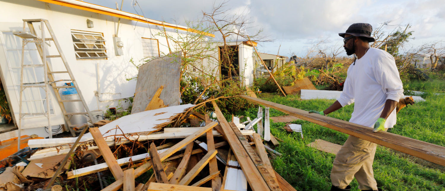 Neil Galloway piles up debris from his and his neighbors' houses in the back yard of his badly damaged property, 13 days after Hurricane Maria raked Whim Estate in the hard-hit Frederiksted area of St. Croix, U.S. Virgin Islands October 1, 2017. (PHOTO: REUTERS/Jonathan Drake)