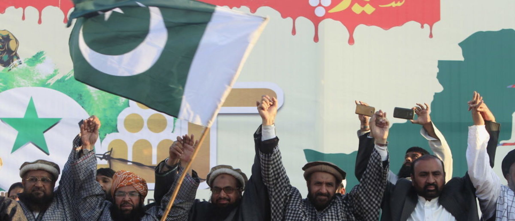A boy waves a Pakistani flag in front of Hafiz Muhammad Saeed (C) chief of the Jamat-ud-Dawa organisation, as Saeed joins hands with leaders of different political parties during a rally to mark Kashmir Solidarity Day, in Islamabad, Pakistan, February 5, 2016. (Photo: REUTERS/Faisal Mahmood)