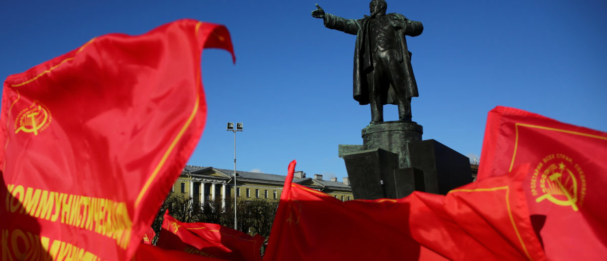 Flags flutter in front of a monument to Soviet state founder Vladimir Lenin during a rally held by Russian Communist Party supporters to mark the Red October revolution's centenary in St. Petersburg, Russia November 7, 2017. REUTERS/Anton Vaganov