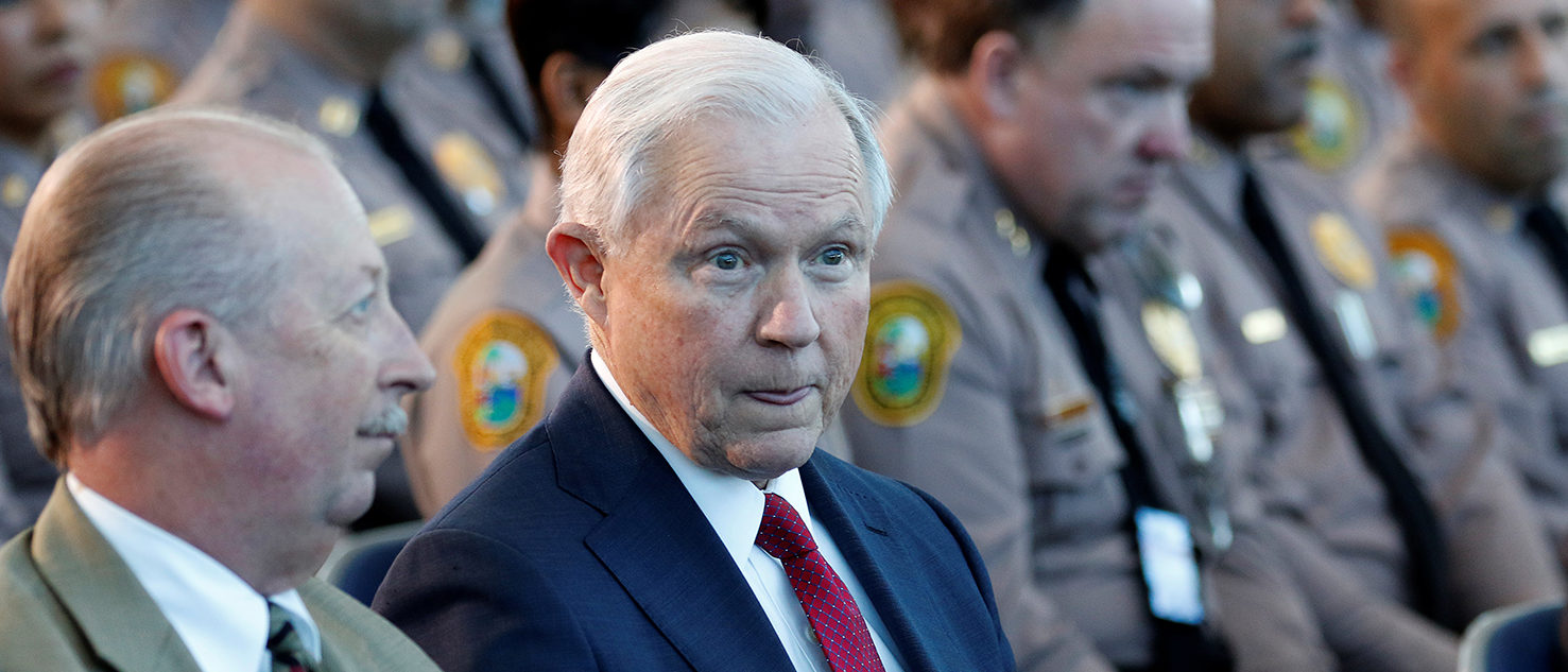 U.S. Attorney General Jeff Sessions (C) sits with guests before speaking on the growing trend of violent crime in sanctuary cities during an event on the Port of Miami in Miami, Florida, U.S., August 16, 2017. REUTERS/Joe Skipper