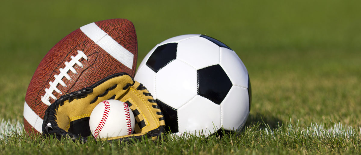 Sports balls on the field with yard line. (Shutterstock/Guzel Studio)