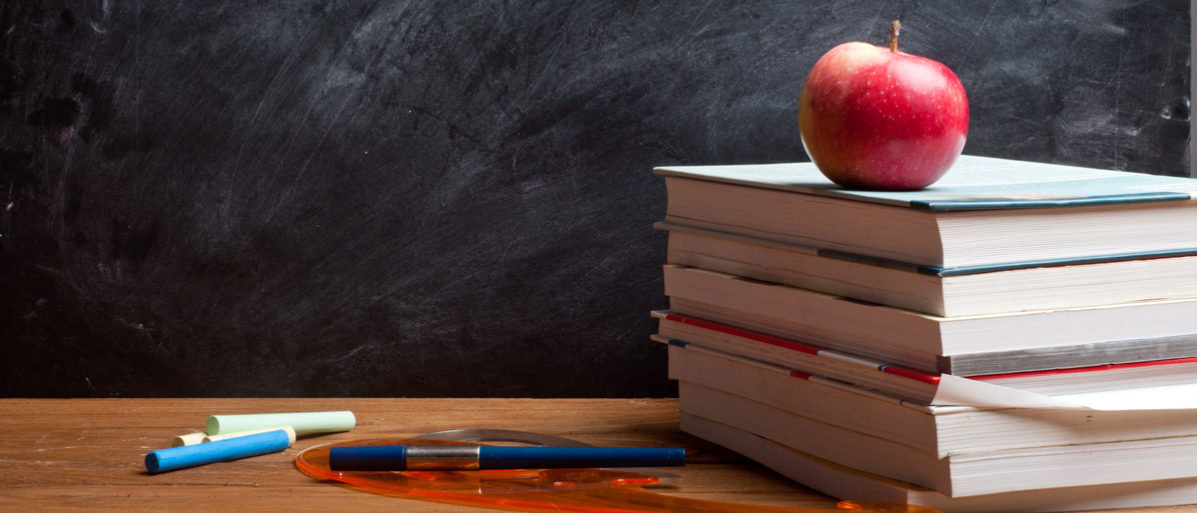 red apple resting on the book with chalk board as background Bartek Zyczynski (Shutterstock)