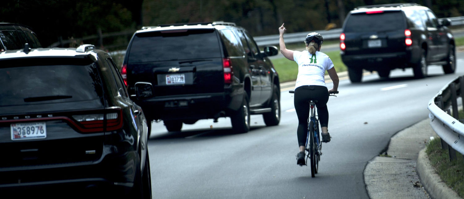 A woman on a bike gestures with her middle finger as a motorcade with US President Donald Trump departs Trump National Golf Course October 28, 2017 in Sterling, Virginia. (Photo: BRENDAN SMIALOWSKI/AFP/Getty Images)