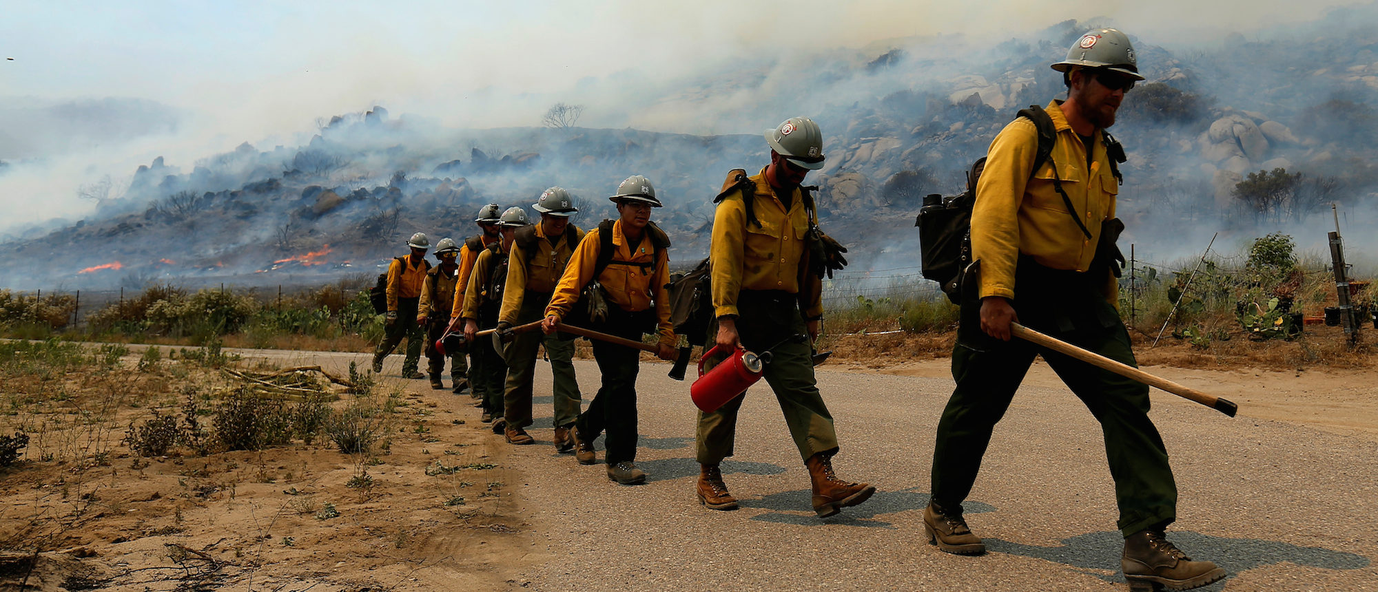 U.S. Forest Service firefighters walk to their truck after battling a wildfire near Potrero California, June 20, 2016. REUTERS/Mike Blake