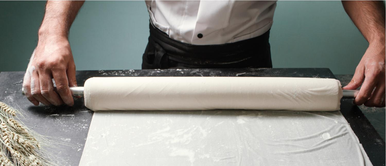 A baker rolls out pastry dough (Photo: Shutterstock/golubovystock)
