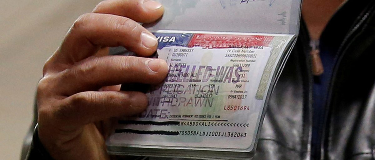 A member of the Al Murisi family, Yemeni nationals who were denied entry into the U.S. because of the travel ban, shows the cancelled visa in their passport from their failed entry to reporters as they successfully arrive to be reunited with their family at Washington Dulles International Airport in Chantilly, Virginia, U.S., February 6, 2017. REUTERS/Jonathan Ernst/Files
