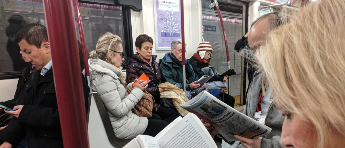 Morning commuters read while riding the TTC Subway in Toronto, Ontario, Canada, November 16, 2017.  REUTERS/Hyungwon Kang