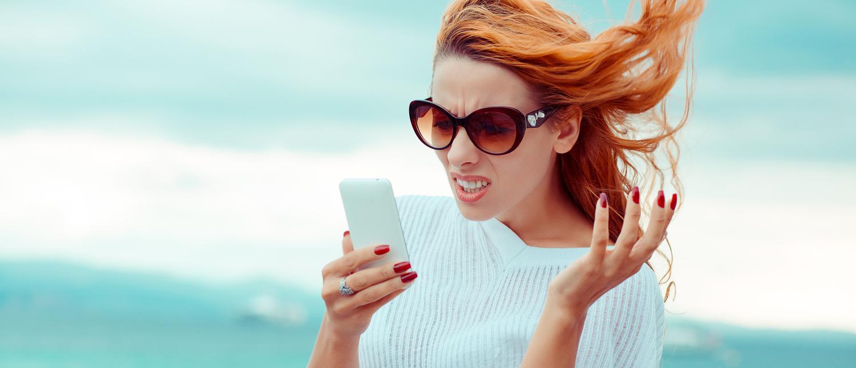 An exasperated woman looks at her cellphone. (Photo: Shutterstock/ HBRH)