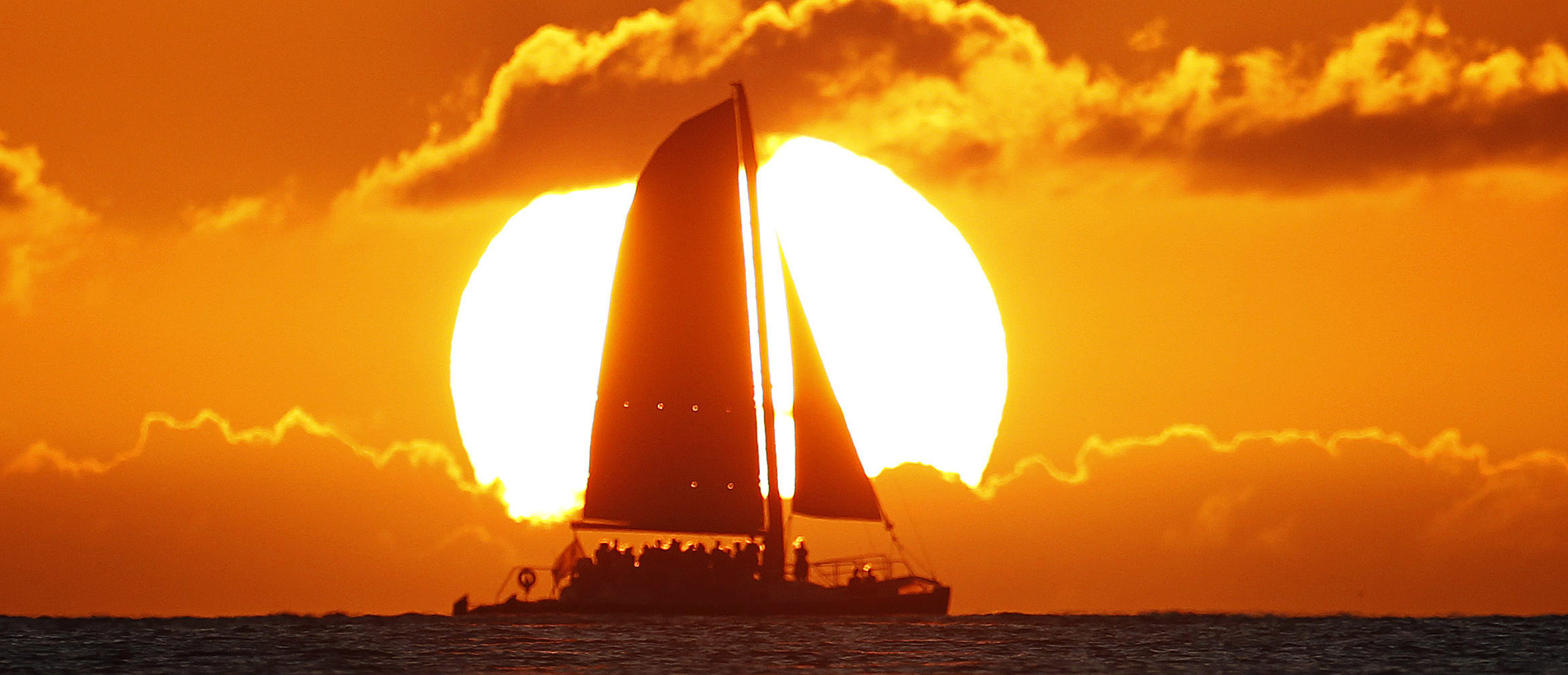 A sail boat passes in front of the sun as the last rays of sunlight of 2011 hit the waters off Waikiki Beach in Honolulu, Hawaii, December 31, 2011. Hawaii is one of the last places on earth that will usher in the New Year. REUTERS/Jason Reed (UNITED STATES - Tags: SOCIETY TPX IMAGES OF THE DAY) - GM1E8110Z8E01