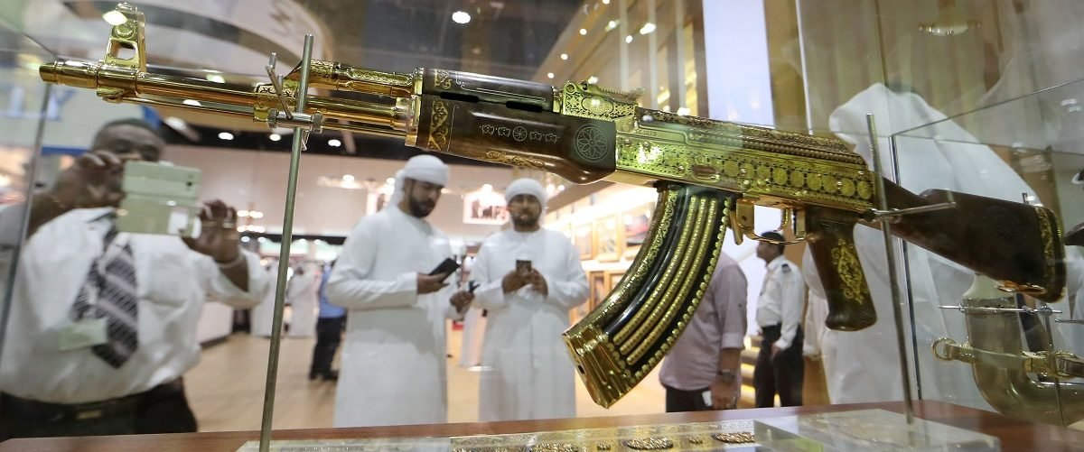 A picture taken on September 14, 2017 shows Emirati men using their cell-phones to take pictutres of an ornamented gold-plated Kalashnikov AK-47 assault rifle on display at the Abu Dhabi International Hunting and Equestrian exhibition (ADIHEX) in the UAE capital. Karim Sahib/AFP/Getty Images.