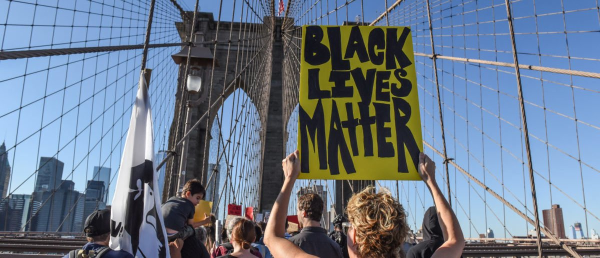 A person carrying a Black Lives Matter sign participates in a protest called March for Racial Justice while walking over the Brooklyn Bridge in New York City, U.S. October 1, 2017. REUTERS/Stephanie Keith
