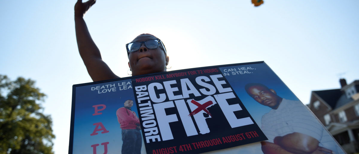 """A relative of a gun violence victim holds a sign at the """"Stop the Violence"""" rally at the intersection of Edmondson Avenue and Wildwood Parkway during the 72 hour community-led Baltimore Ceasefire against gun violence in Baltimore, Maryland, U.S. August 4, 2017. REUTERS/Sait Serkan Gurbuz"""