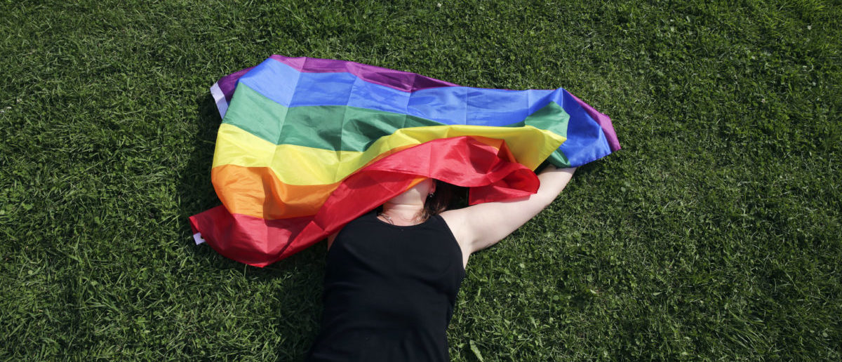 "A woman with a rainbow flag lays on grass during the LGBT (lesbian, gay, bisexual, and transgender) community rally ""VIII St.Petersburg Pride"" in St. Petersburg, Russia August 12, 2017. (Photo: REUTERS/Anton Vaganov)"