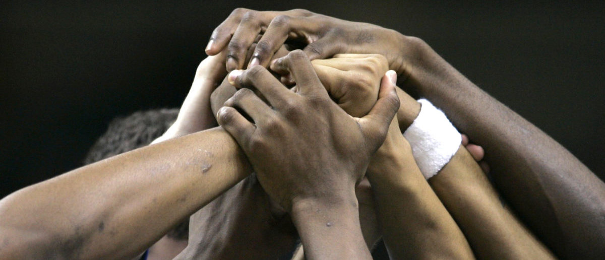 University of Kansas Jayhawks' players put their hands together at the end of a timeout while playing the UCLA Bruins in their NCAA men's West Regional final basketball game in San Jose, California March 24, 2007. REUTERS/Mike Blake