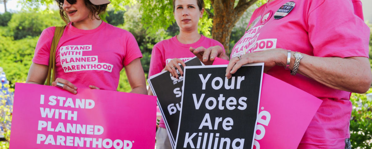 Supporters of Planned Parenthood hold signs during a rally to fight back against the U.S. House of Representatives' vote to repeal the Affordable Care Act held outside of the office of Congressman Steve Knight in Santa Clarita, Los Angeles, California, U.S., May 4, 2017. REUTERS/Andrew Cullen
