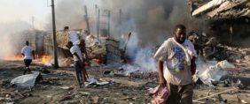 Civilians walk at the scene of an explosion in Mogadishu