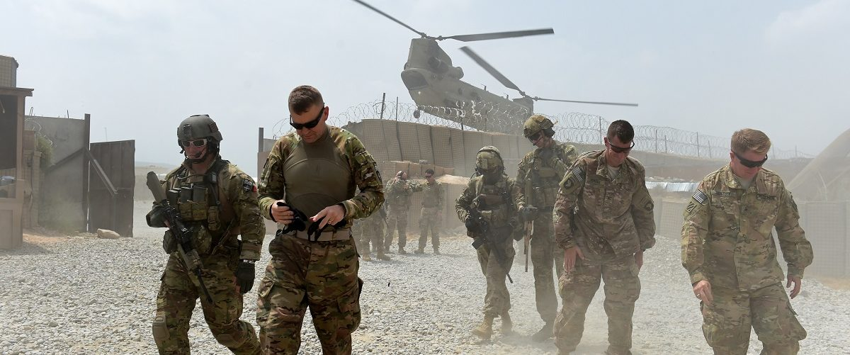 """In this photograph taken on August 13, 2015, US army soldiers walk as a NATO helicopter flies overhead at coalition force Forward Operating Base (FOB) Connelly in the Khogyani district in the eastern province of Nangarhar. From his watchtower in insurgency-wracked eastern Afghanistan, US army Specialist Josh Whitten doesn't have much to say about his Afghan colleagues. """"They don't come up here anymore, because they used to mess around with our stuff. """"Welcome to Forward Operating Base Connelly, where US troops are providing training and tactical advice to the 201st Afghan army corps as they take on the Taliban on the battlefield. Wakil Kohsar/AFP/Getty Images."""