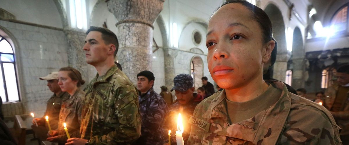 US Soldiers attend a Christmas Eve service for Iraqi Christians at the Saint John's church (Mar Yohanna church) in the town of Qaraqosh (also known as Hamdaniya), 30 kms east of Mosul, on December 25, 2016. Safin Hamed/AFP/Getty Images.