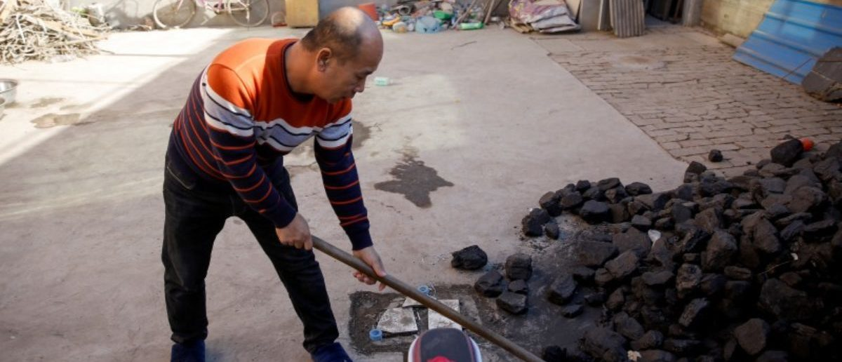 A man shovels coal he uses to heat his home in his courtyard in the village of Heqiaoxiang