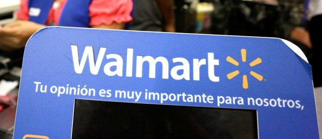 """FILE PHOTO: A cashier smiles beyond a Walmart logo during the kick-off of the 'El Buen Fin' (The Good Weekend) holiday shopping season, at a Walmart store in Monterrey, Mexico, November 17, 2017.  The sign reads """"Your opinion is very important to us."""" REUTERS/Daniel Becerril/File Photo"""