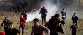 Palestinian protesters run for cover during clashes with Israeli troops as Palestinians call for a