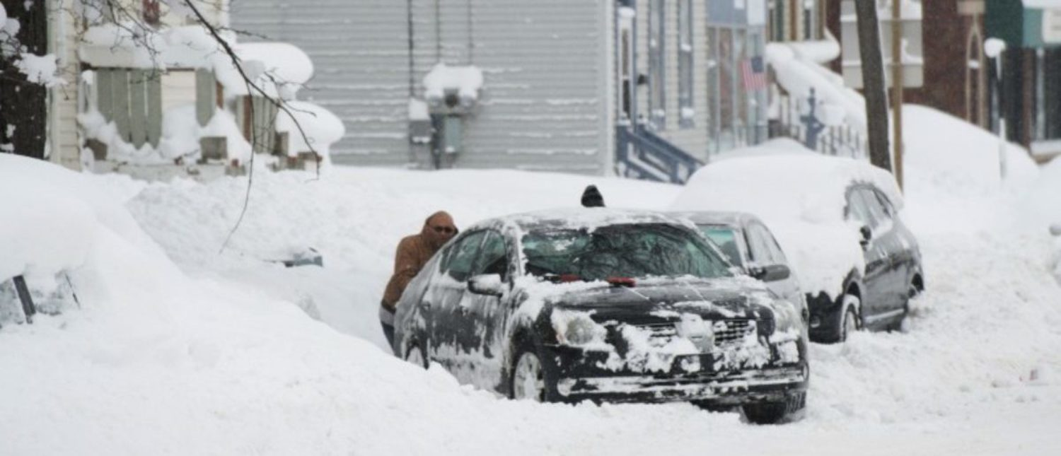 People help dig out a car from a parking spot after two days of record-breaking snowfall in Erie