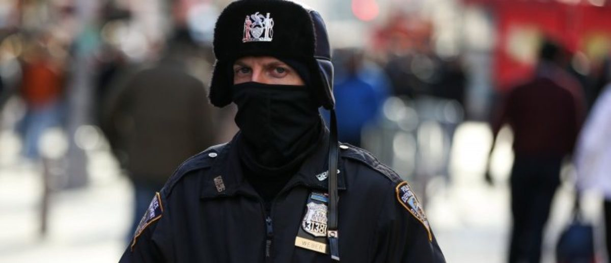 A New York Police Department (NYPD) officer bundles up against the cold temperature as he walks in Times Square in Manhattan, New York, U.S., December 28, 2017. REUTERS/Amr Alfiky